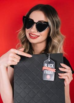 Ładna kobieta wskazuje na torbie od czarnego piątku