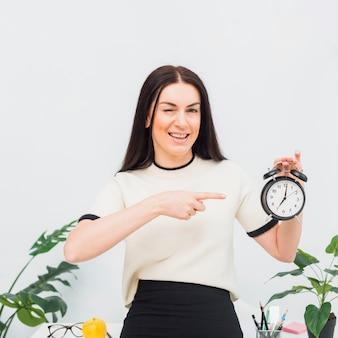 Ładna kobieta wskazuje palec przy zegarem
