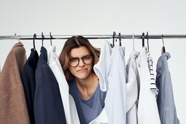 Ładna kobieta wybór ubrań w pobliżu jasnego tła garderoby