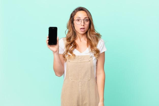 Ładna kobieta wygląda na bardzo zszokowaną lub zaskoczoną i trzyma smartfon