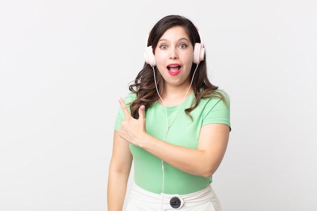 Ładna kobieta wygląda na podekscytowaną i zaskoczoną, wskazując na bok, słuchając muzyki przez słuchawki