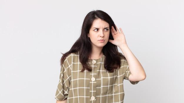 Ładna kobieta wygląda na poważną i zaciekawioną, słucha, próbuje podsłuchać tajną rozmowę lub plotki, podsłuchuje