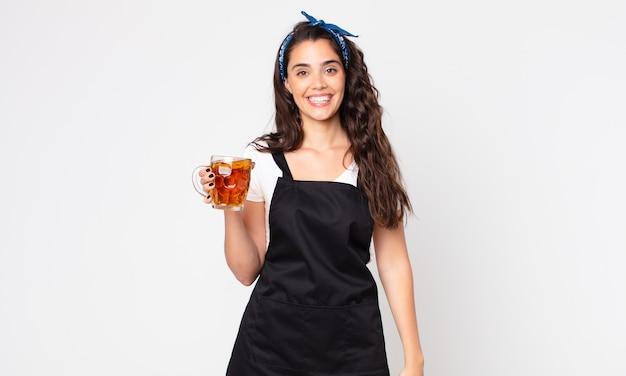 Ładna kobieta wygląda na szczęśliwą i mile zaskoczoną, trzymając kufel piwa
