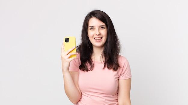 Ładna kobieta wygląda na szczęśliwą i mile zaskoczoną używając smartfona