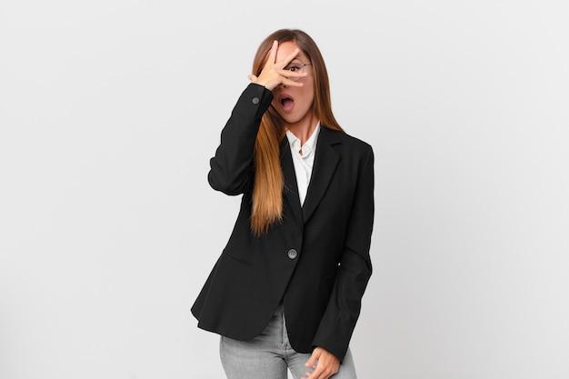 Ładna kobieta wygląda na zszokowaną, przestraszoną lub przerażoną, zakrywając twarz dłonią. pomysł na biznes