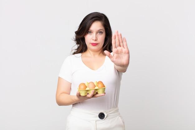 Ładna kobieta wygląda poważnie pokazując otwartą dłoń, wykonując gest zatrzymania i trzymając pudełko z jajkami