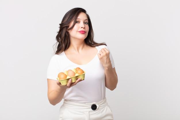 Ładna kobieta wyglądająca arogancko, odnosząca sukcesy, pozytywna i dumna, trzymająca pudełko z jajkami