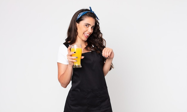 Ładna kobieta wyglądająca arogancko, odnosząca sukcesy, pozytywna i dumna, trzymająca szklankę soku pomarańczowego