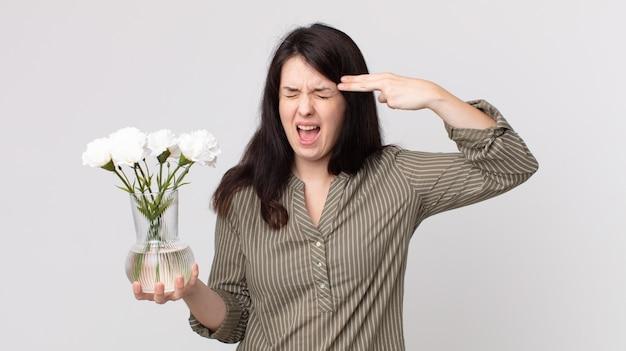 Ładna kobieta wyglądająca na niezadowoloną i zestresowaną, samobójczy gest robiący znak pistoletu i trzymający ozdobne kwiaty. asystent agenta z zestawem słuchawkowym