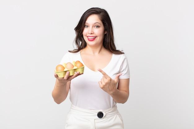 Ładna kobieta wyglądająca na podekscytowaną i zaskoczoną, wskazując na bok i trzymająca pudełko z jajkami