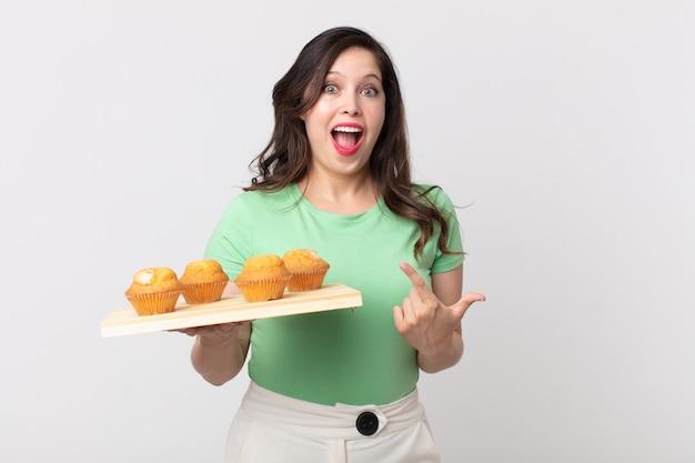Ładna kobieta wyglądająca na podekscytowaną i zaskoczoną, wskazującą na bok i trzymającą tacę z babeczkami