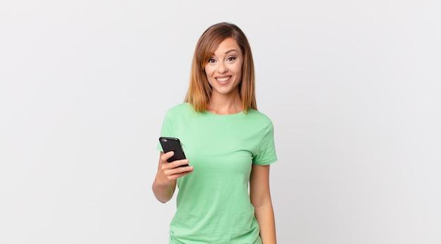 Ładna kobieta wyglądająca na szczęśliwą i mile zaskoczoną i korzystająca ze smartfona