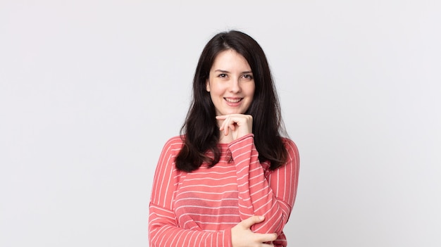 Ładna kobieta wyglądająca na szczęśliwą i uśmiechnięta z ręką na brodzie, zastanawiająca się lub zadająca pytanie, porównująca opcje