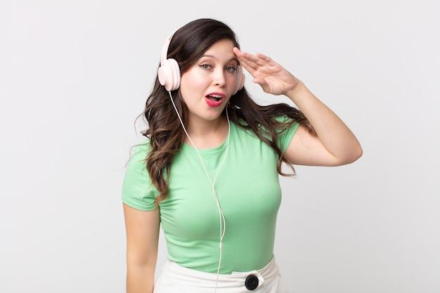 Ładna kobieta wyglądająca na szczęśliwą, zdumioną i zaskoczoną słuchaniem muzyki przez słuchawki