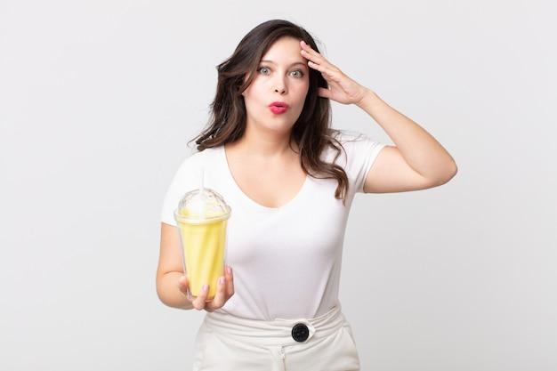 Ładna kobieta wyglądająca na szczęśliwą, zdziwioną i zaskoczoną, trzymającą waniliowy koktajl mleczny