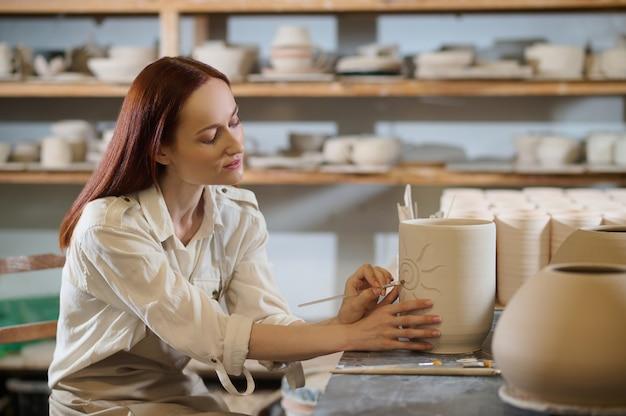 Ładna kobieta wyglądająca na zaangażowaną podczas malowania doniczki