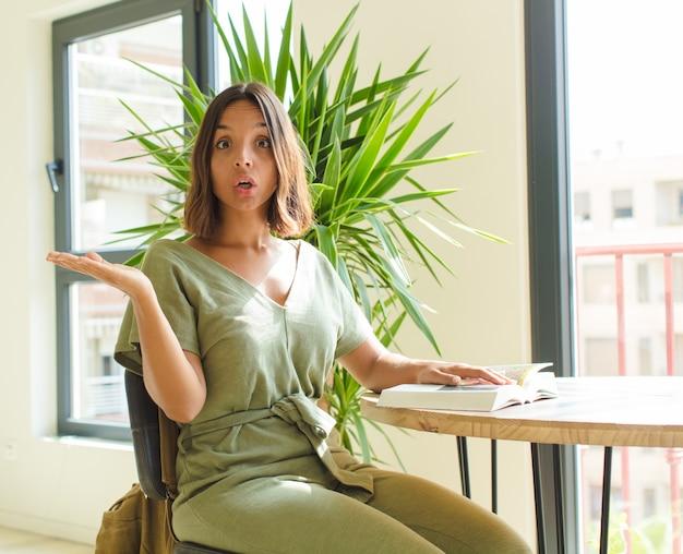 Ładna kobieta wyglądająca na zaskoczoną i zszokowaną, z opadniętą szczęką trzymającą przedmiot z otwartą ręką z boku