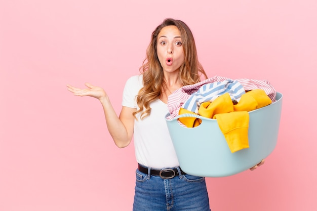 Ładna kobieta wyglądająca na zaskoczoną i zszokowaną, z opuszczoną szczęką, trzymająca przedmiot i piorącą ubrania.