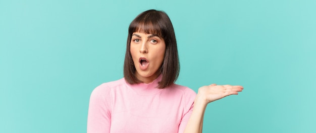 Ładna kobieta wyglądająca na zaskoczoną i zszokowaną, z opuszczoną szczęką, trzymająca przedmiot z otwartą dłonią z boku