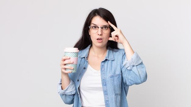Ładna kobieta wyglądająca na zaskoczoną, realizująca nową myśl, pomysł lub koncepcję i trzymająca kawę na wynos