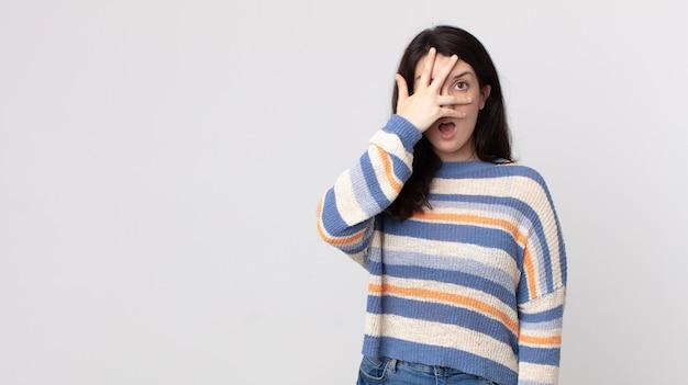 Ładna kobieta wyglądająca na zaszokowaną, przestraszoną lub przerażoną, zakrywa twarz dłonią i zerka między palcami