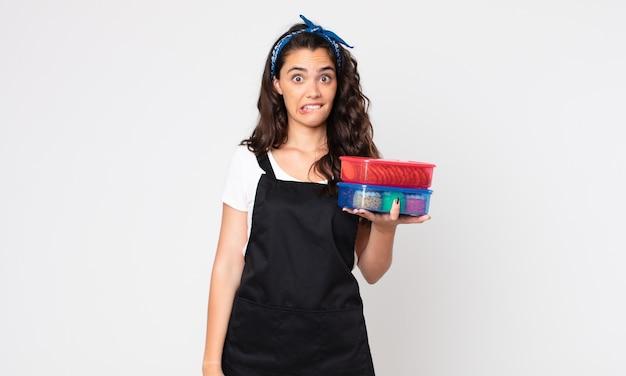 Ładna kobieta wyglądająca na zdziwioną i zdezorientowaną, trzymająca tupperware z jedzeniem