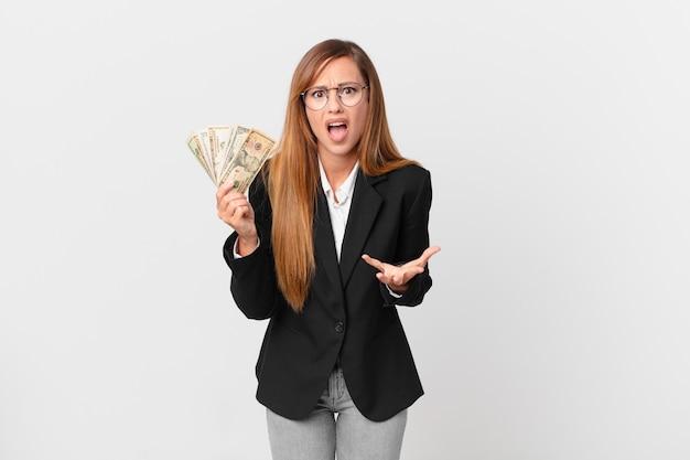 Ładna kobieta wyglądająca na złą, zirytowaną i sfrustrowaną. koncepcja biznesu i dolarów