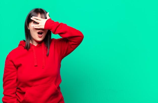 Ładna kobieta wyglądająca na zszokowaną, przestraszoną lub przerażoną, zakrywającą twarz dłonią i zaglądającą między palce