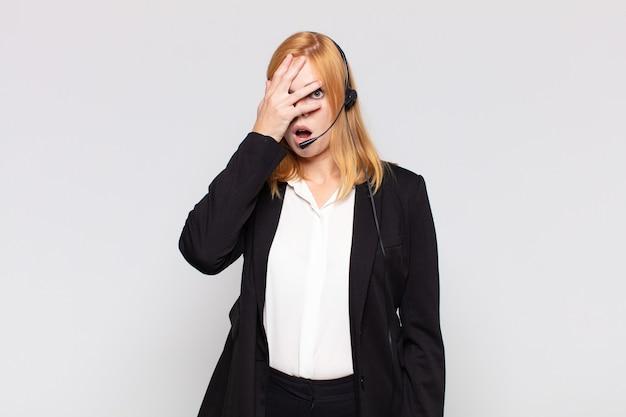 Ładna kobieta wyglądająca na zszokowaną, przestraszoną lub przerażoną, zakrywająca twarz ręką i zaglądająca między palce