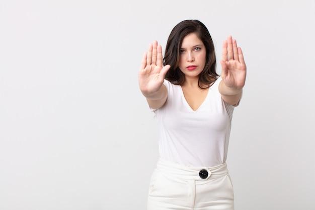 """Ładna kobieta wyglądająca poważnie, nieszczęśliwa, zła i niezadowolona, zakazująca wejścia lub mówiąca """"stop"""" z obiema otwartymi dłońmi"""