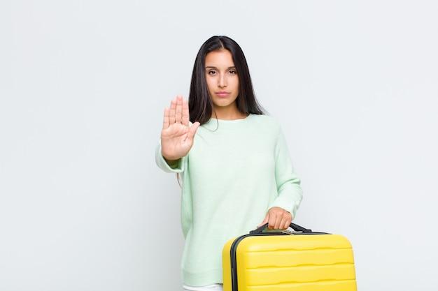 Ładna kobieta wyglądająca poważnie, surowo, niezadowolona i zła, pokazując otwartą dłoń wykonującą gest stop