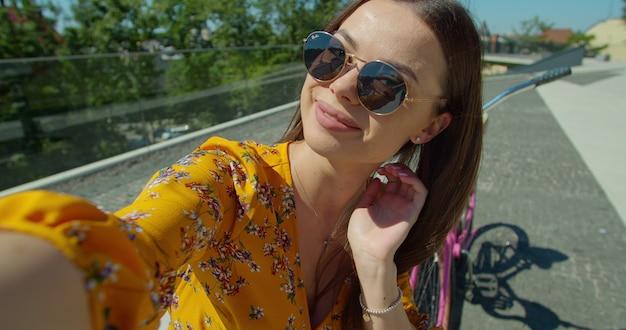 Ładna kobieta wykonuje rozmowę wideo w parku w słoneczny dzień. młoda kobieta za pomocą smartfona do nawiązywania połączeń wideo, siedząc na ławce.