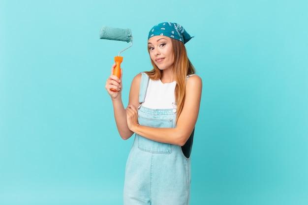 Ładna kobieta wzrusza ramionami, czuje się zdezorientowana i niepewna malując nową ścianę domu