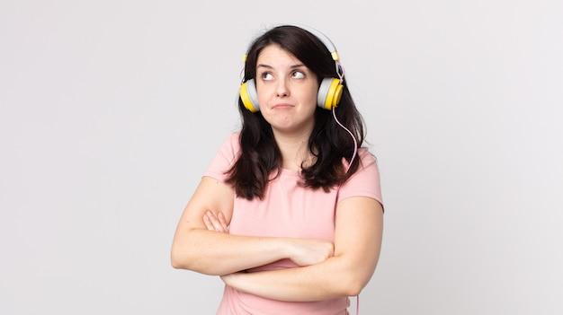 Ładna kobieta wzrusza ramionami, czuje się zdezorientowana i niepewna słuchając muzyki przez słuchawki
