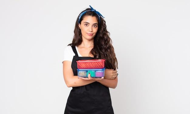 Ładna kobieta wzrusza ramionami, czuje się zdezorientowana i niepewna, trzymając tupperware z jedzeniem