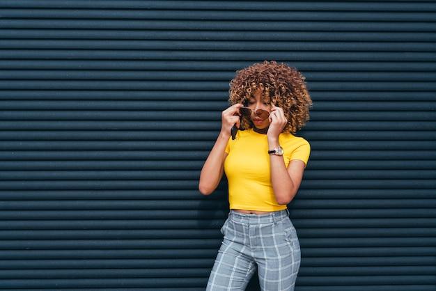 Ładna kobieta z afro pozuje w ulicie