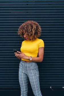 Ładna kobieta z afro włosy używać telefon komórkowego.