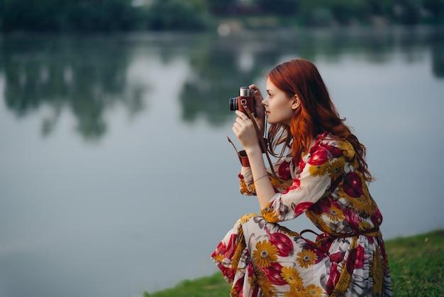 Ładna kobieta z aparatem w pobliżu rekreacji na świeżym powietrzu nad jeziorem
