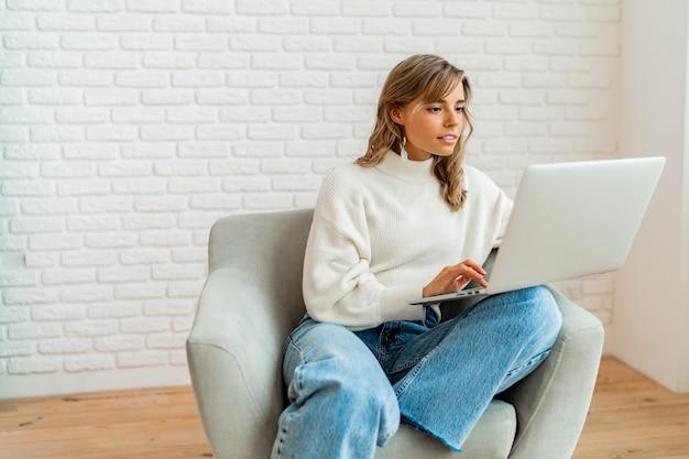 Ładna kobieta z blond falującymi włosami, siedząca na kanapie w domu, pracująca na laptopie