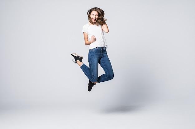 Ładna kobieta z brązowymi długimi włosami i szczęśliwy uśmiechnięty wyraz twarzy, skacząc w studio na białym tle
