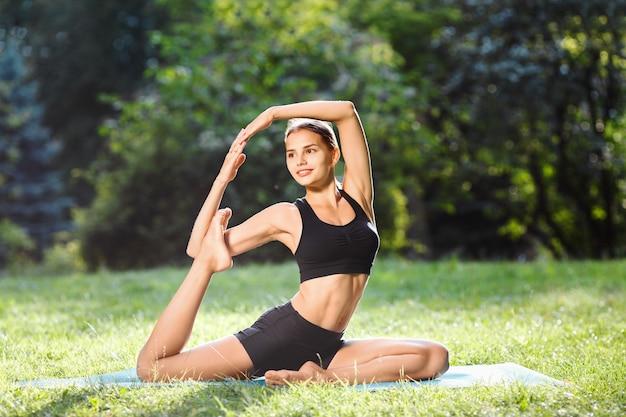 Ładna kobieta z brązowymi włosami na sobie czarny top i spodenki robi pozycję jogi w parku, zdrowy styl życia, natura