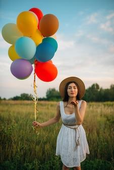 Ładna kobieta z bukietem kolorowych balonów wysyła buziaka