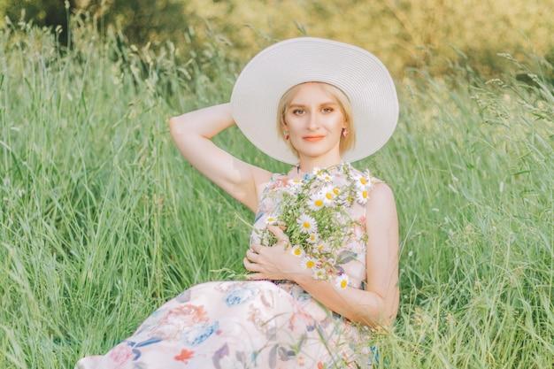 Ładna kobieta z bukietem stokrotek na tle wysokiej trawy w sezonie letnim