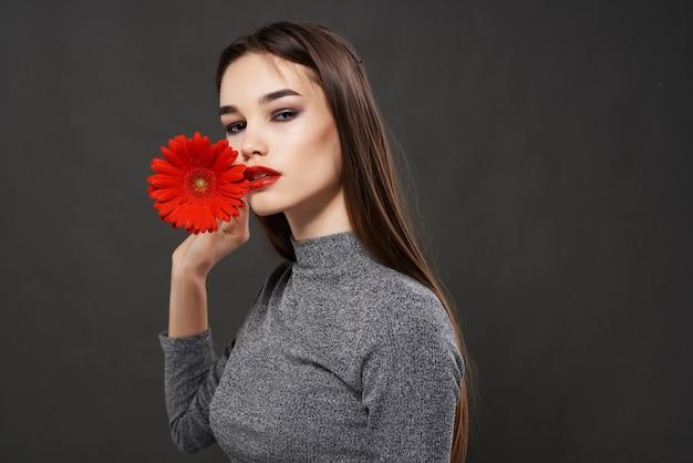 Ładna kobieta z czerwonym kwiatem usta jasne studio makijażu