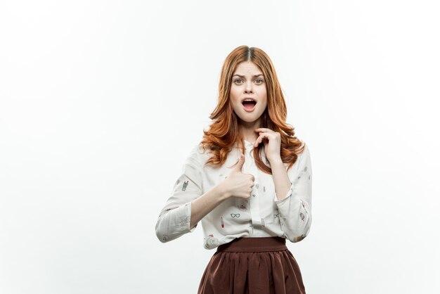 Ładna kobieta z czerwonymi włosami w garniturze gestykuluje z rękami uśmiechem