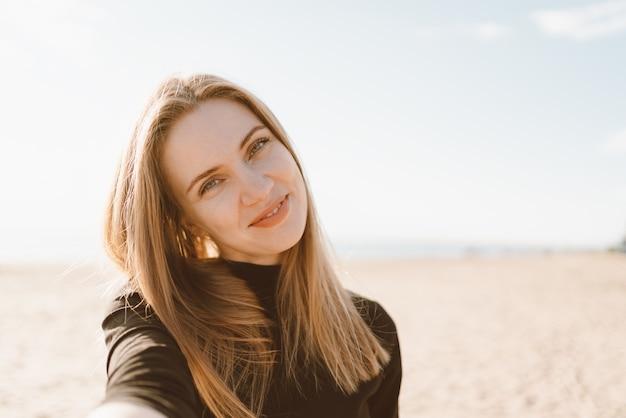 Ładna kobieta z długimi włosami bierze selfie na smartfonie na plaży latem lub jesienią.