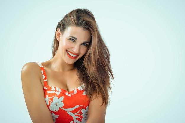 Ładna kobieta z długimi włosami i słodkim uśmiechem odizolowana w pomarańczowej sukience z białymi kwiatami