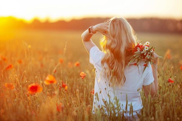 Ładna kobieta z długimi włosami na polu maku o zachodzie słońca.
