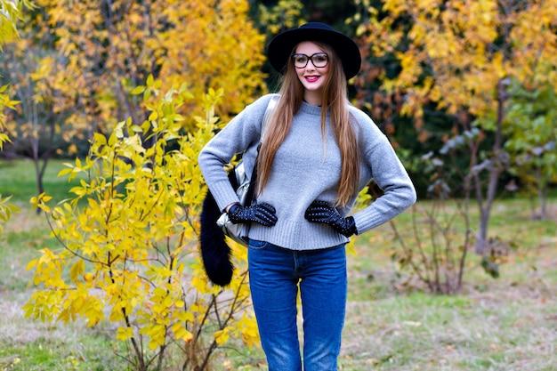 Ładna kobieta z długimi włosami nosi dżinsy i rękawiczki stojąc w pewnej pozie na tle przyrody. zewnątrz zdjęcie ładnej modelki w modnym szarym swetrze spaceru w parku w jesienny dzień.