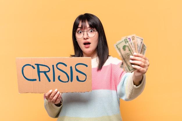 Ładna kobieta z dolarowymi banknotami i tablicą kryzysową